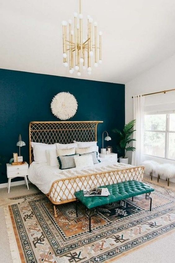 a pretty mid-century modern bedroom with a gilded bed, neutral and printed bedding, a gold chandelier, a turquoise bench, a printed rug and a potted plant