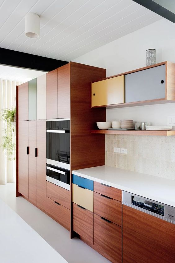 a pretty mid-century modern kitchen with rich-stained cabinets, colorful drawers and storage units, a neutral tile backsplash