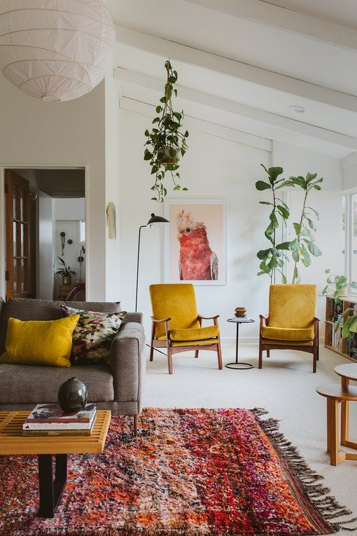 a pretty mid-century modern living room with a grey sofa, mustard chairs and pillows, a colorful rug, potted plants and round tables