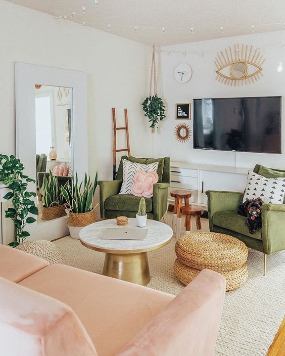 a pretty mid-century modern living room with grene chairs, a blush loveseat, a round table and woven poufs, potted plants and lights