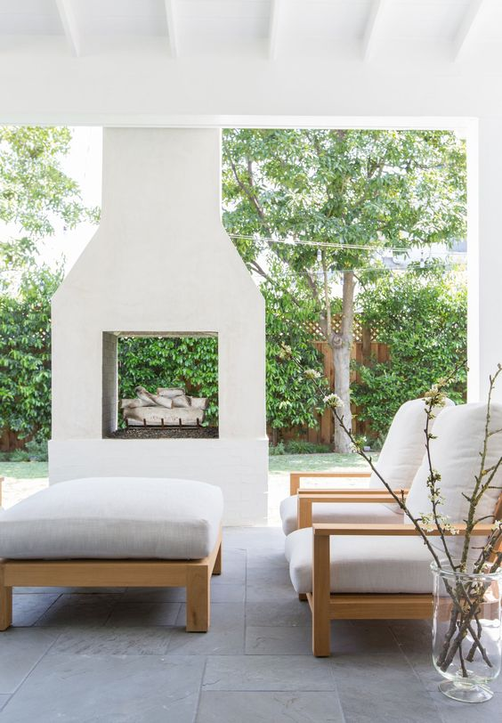 a pretty modern outdoor space clad with tiles, with a two-sided white fireplace, simple chairs and a low ottoman plus a lovely view of the garden