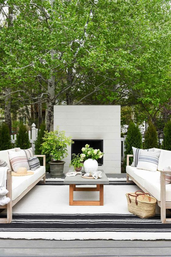 a pretty modern terrace with a white fireplace, neutral sofas and a concrete coffee table, printed textiles and potted greenery and blooms