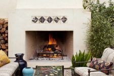a pretty outdoor space wiht a large stucco fireplace, dark stained furniture with printed textiles, lots of greenery and blooms and firewood