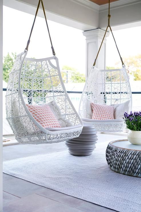 a pretty small patio with cool white hanging chairs with printed pillows, side tables, potted blooms is a very chic space to relax in