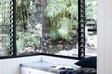 a pretty tropical nook with a corner window and a daybed here that create a very lovely and cozy nook for spending time