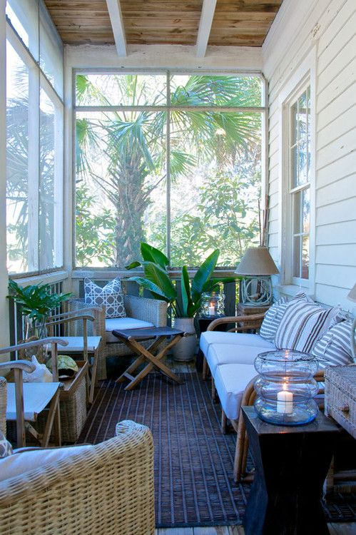 a pretty tropical screened porch with wicker furniture, printed pillows, potted plants, candle lanterns and lamps is cool