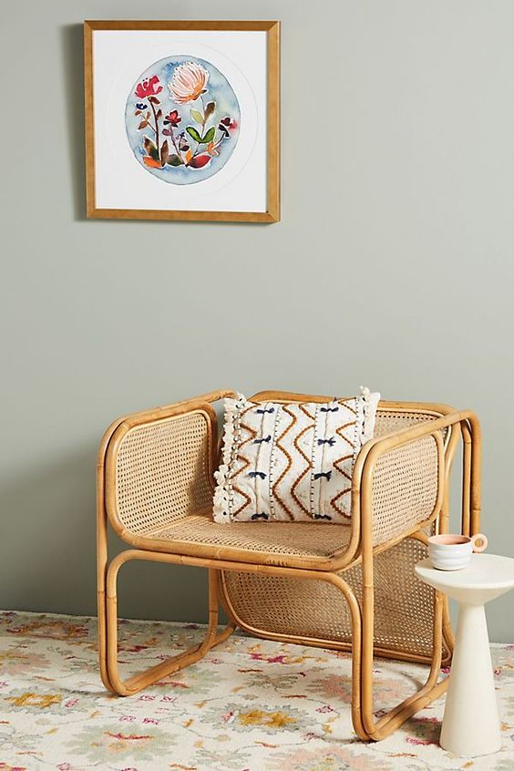 a rattan and cane chair with a printed boho pillow is a gorgeous modern accent piece for any room, it cna fit a modern or a boho interior