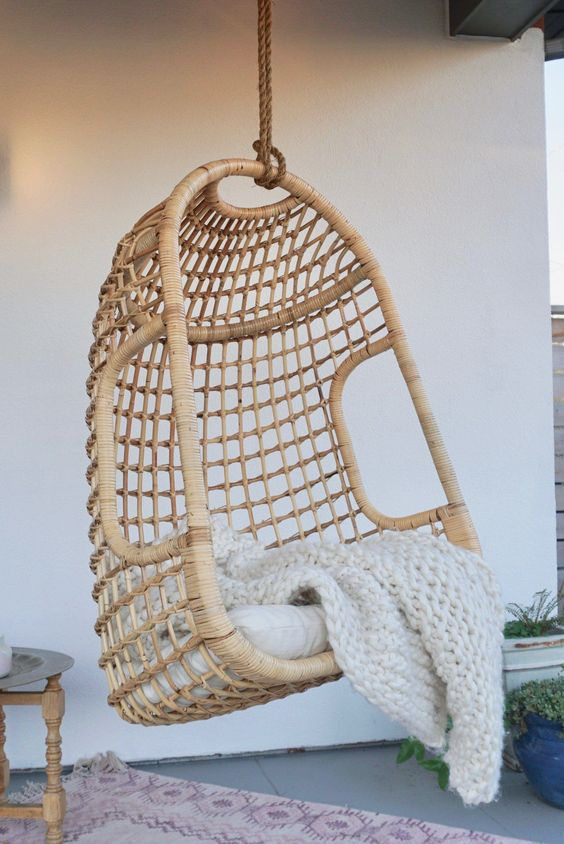 a rattan suspended chair with a cushion and a knit blanket is a lovely piece for any contemporary outdoor space
