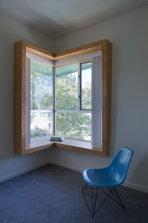 a reading and studying nook organized around a corner window with heavy framing that serves as a desk and a blue chair