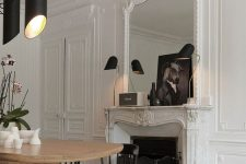 a refined Parisian home office with molding on the walls, ceiling and fireplace, a rounded desk, black chairs, black lamps and art