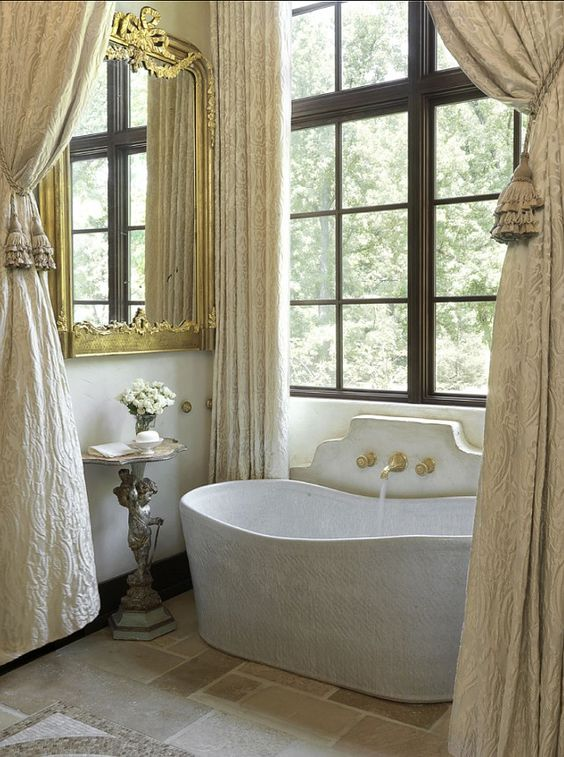 a refined Provence bathroom with a dark stained French window, a stone tub, neutral stone on the floor and neutral textiles and gold touches