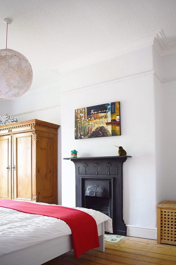 a refined bedroom with a light stained wardrobe, a black metal fireplace, a bed with white bedding and a pretty and bold artwork