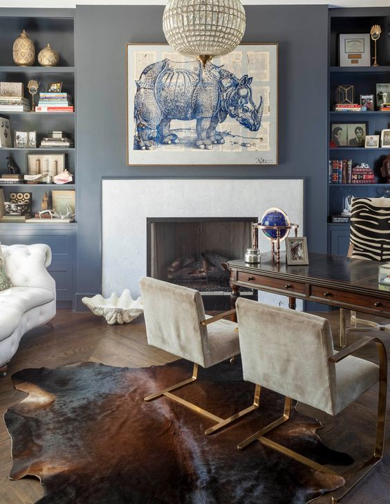 a refined home office with blue walls, built-in shelves, a fireplace, a vintage dark stained desk, grey chairs and a creamy sofa plus art
