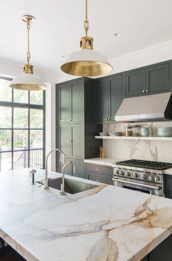 a refined kitchen with dark grey cabinets, a white stone backsplash and countertops, pendan lamps with gold parts and chromatic appliances and fixtures