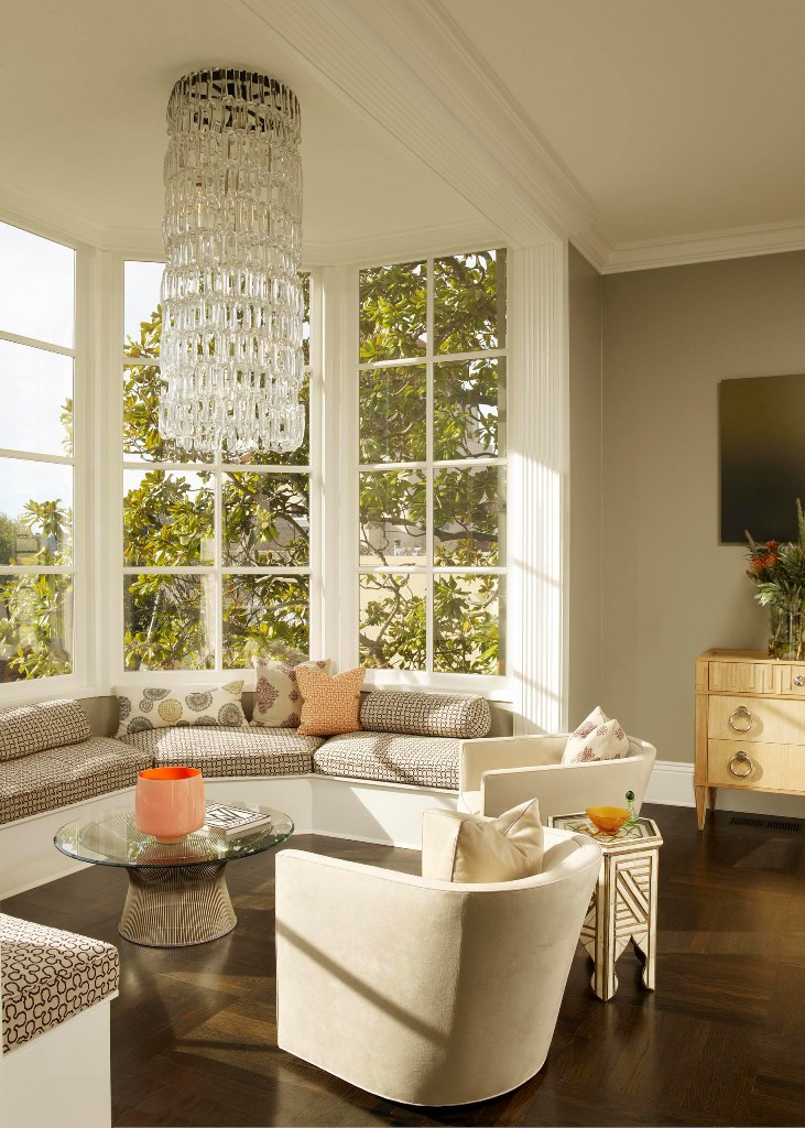 a refined living room with a large curved bow window space that is turned into a seating space with a large built-in daybed, a crystal chandelier and a chair