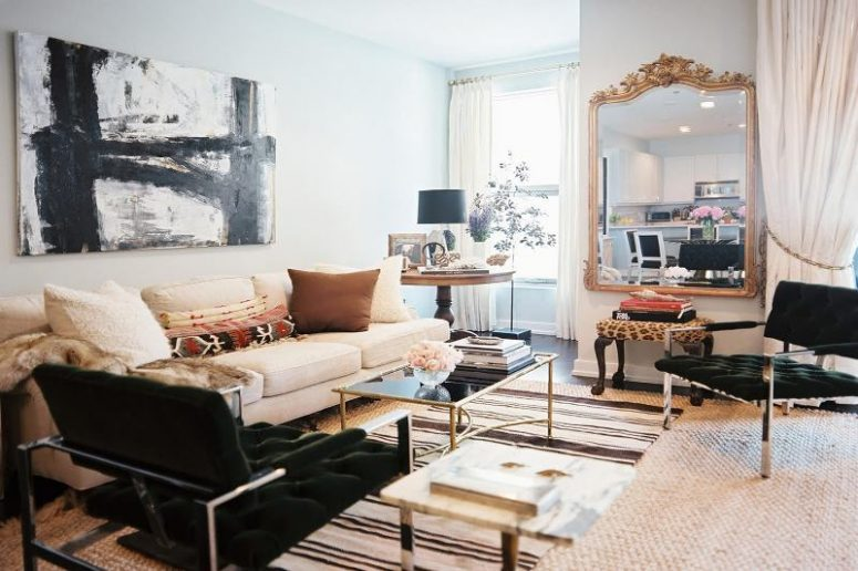 a refined living room with a neutral sofa, a dark green chair, a glass table, an oversized mirror in a gold ornated frame, chairs with chrome legs and armrests