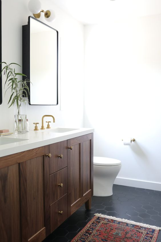 a refined mid-century modern bathroom with black hex tiles, a stained vanity, a printed boho rug, gold fixtures and sconces