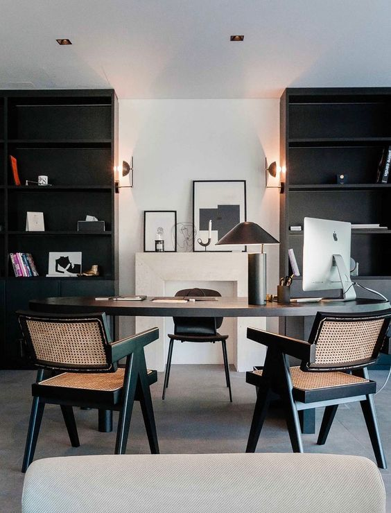 a refined mid-century modern home office with black bookcases, a black desk, black rattan chairs and a cool lamp plus a gallery wall