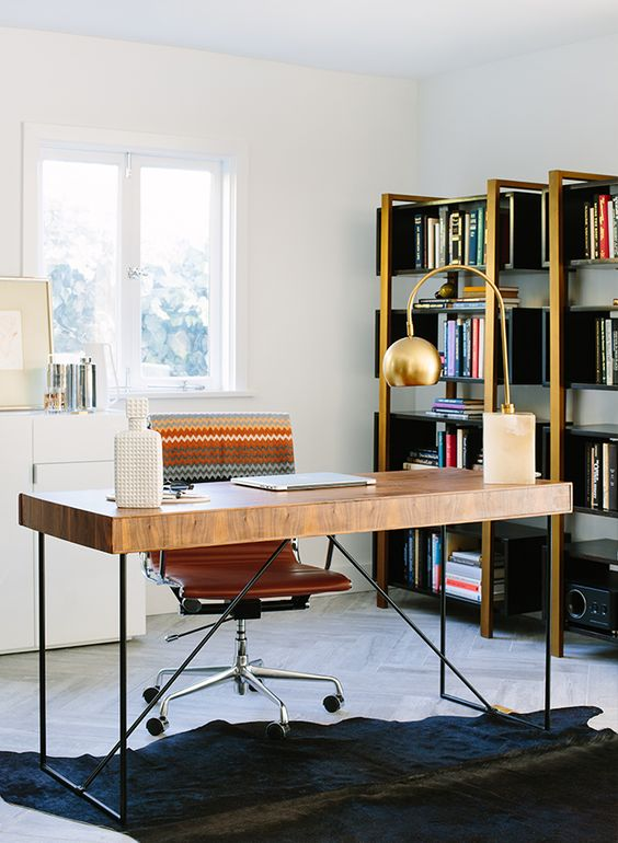 a refined mid-century modern home office with gilded bookcases, a wooden desk, a leather chair, a black rug and a white cabinet for storage
