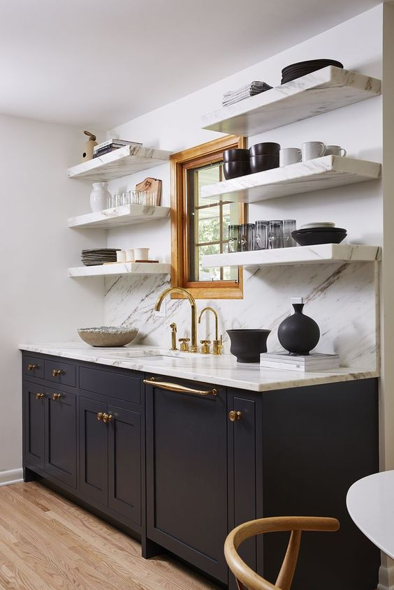 a refined mid-century modern kitchen with dark grey cabinets, open shelves of white stone, a backsplash and countertops
