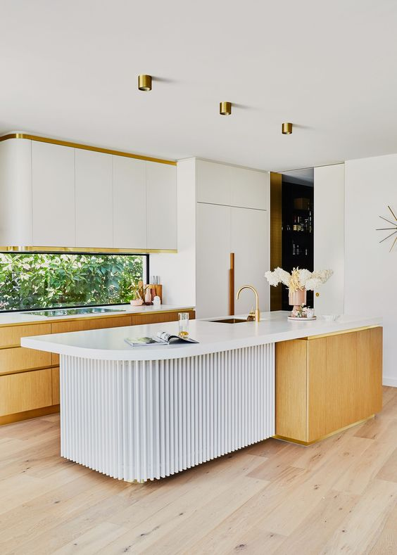 a refined mid-century modern kitchen with white and light-stained cabinets, a window backsplash, a sculptural kitchen island and gold touches