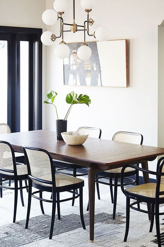 a refined modern dining room with a stained table, black chairs with cane backs and seats, a vintage chandelier and a statement artwork
