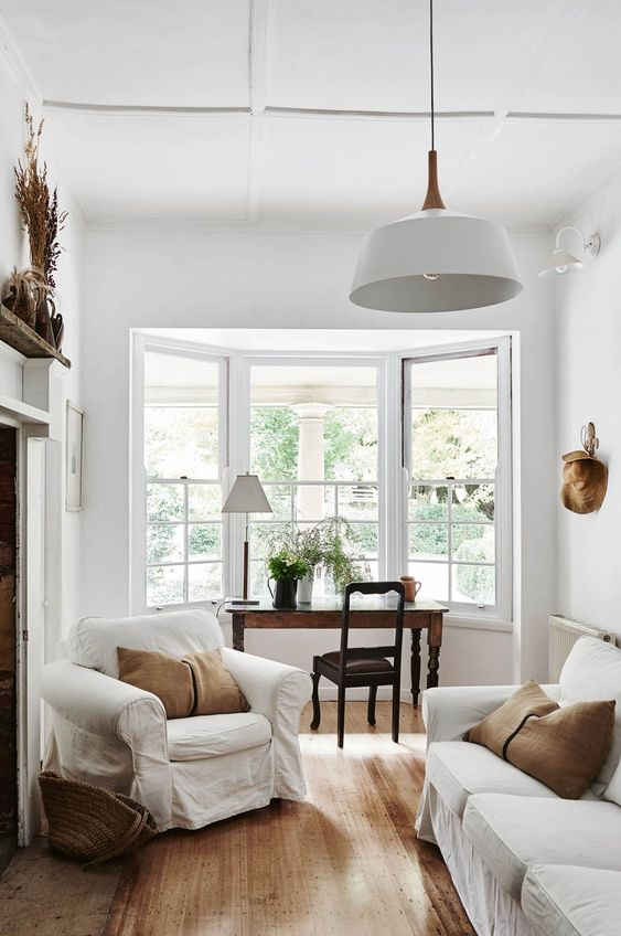 a refined neutral living room with white furniture, rust colored pillows,a vintage desk and chair by the bow window