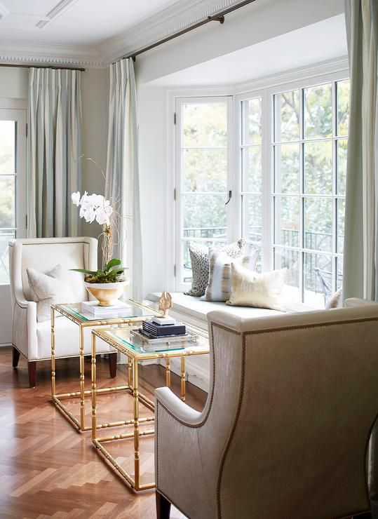 a refined space with a bow window and a daybed on the windowsill, refined chairs and glass and metal tables