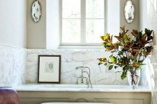 a refined vintage bathroom with a tall French arched window, a tub with paneling, an upholstered ottoman and a leather chair
