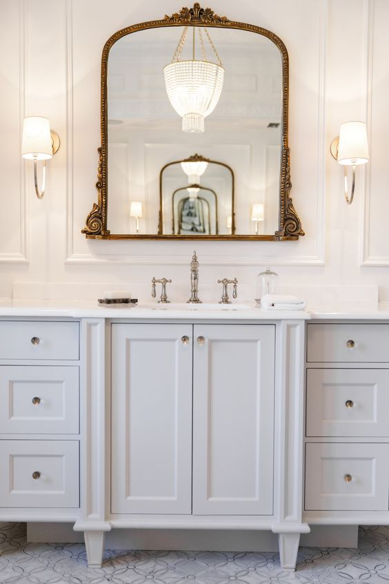 a refined white bathroom with chic cabinets and a vanity, a vintage chromatic faucet, a mirror in a beautiful brass ornated frame, sconces with chromatic legs