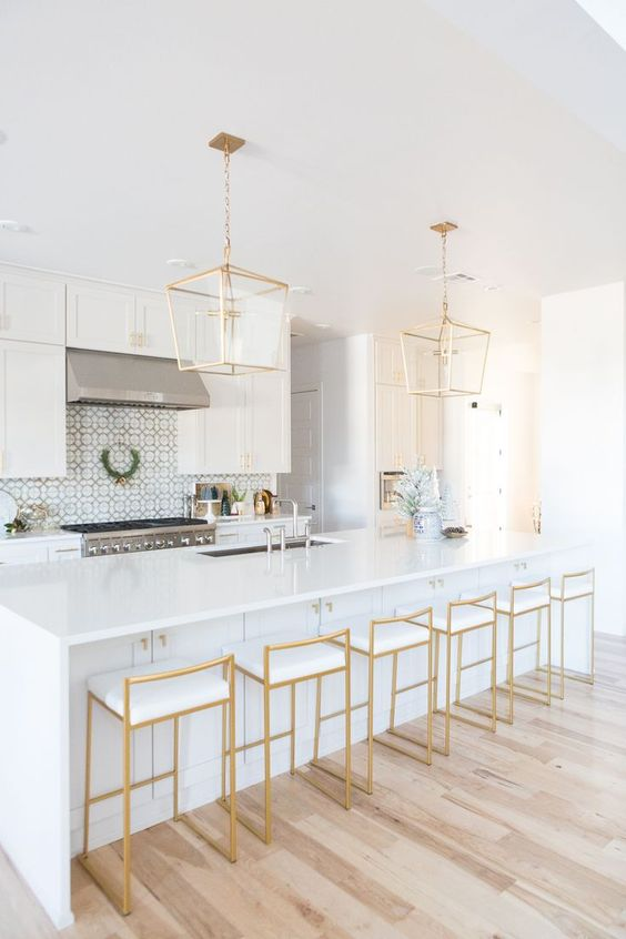 a refined white kitchen with chrome appliances and fixtures and beautiful gold pendant lamps and gold and white stools