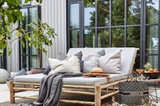 a relaxed deck with a large bamboo daybed with muted pillows and blankets, a side table, trees and greenery and vases