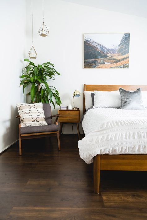 a relaxed mid-century modern bedroom with a dark stained floor, stained furniture, a pretty photo over the bed, pendant lamps and a potted tree