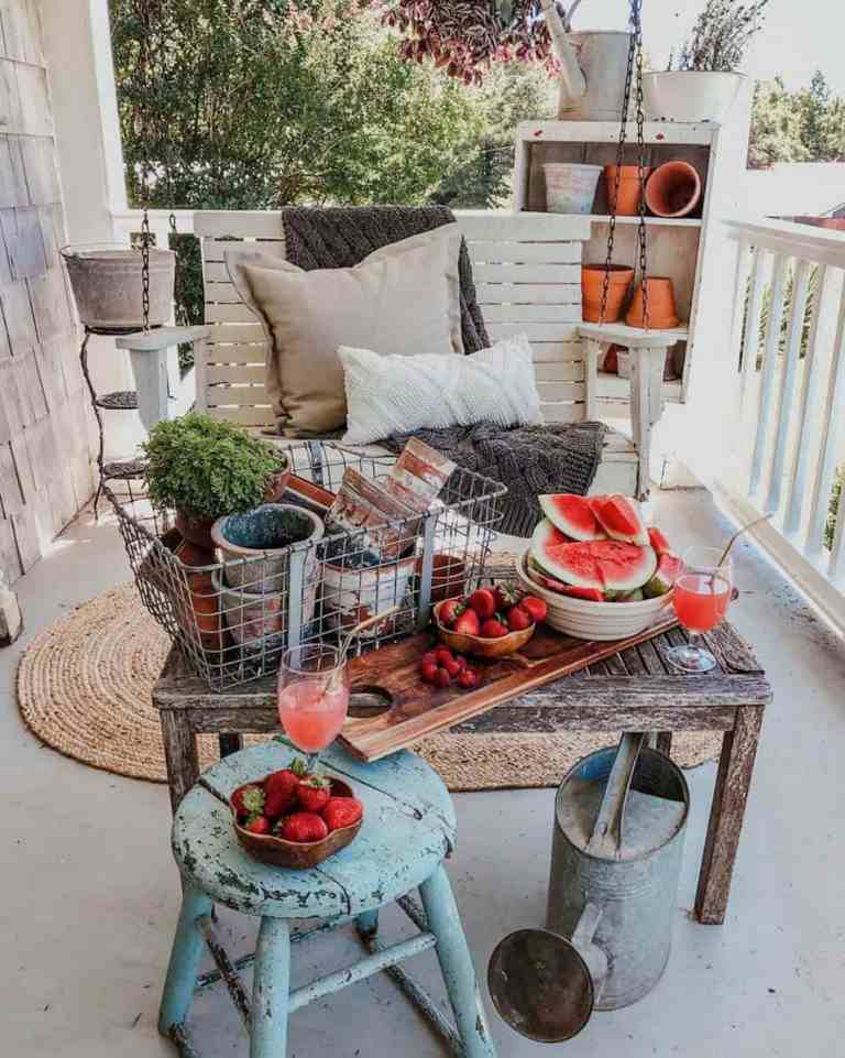 a relaxed rustic porch with a hanging bench, a shabby table with a metal crate and planters, a watering can and a shabby stool
