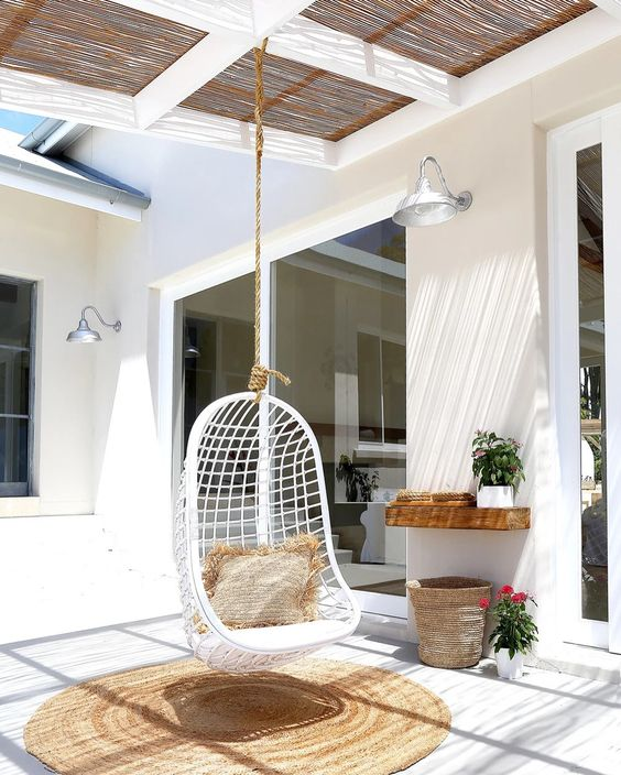 a relaxed tropical outdoor space with a woven roof, a hanging rattan chair with a jute pillow and a rug, an open shelf and potted blooms