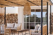 a relaxed tropical patio with a roof, a rock wlal, bamboo and wood furniture, a woven pendant lamp and neutral textiles and upholstery