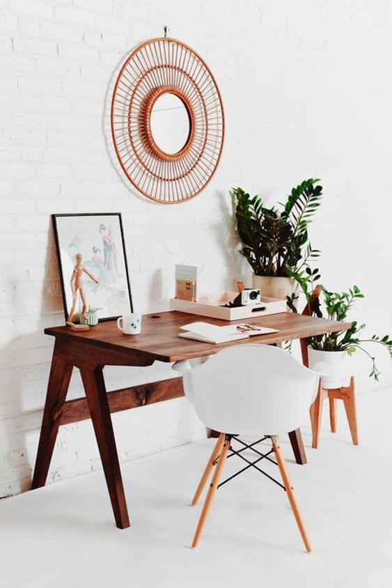 a retro home office with a rich-stained desk, a white chair, a mirror in a woven frame, potted plants on stands is cool