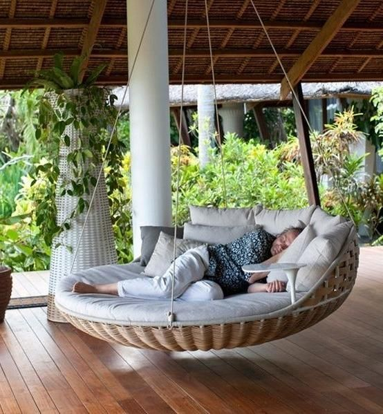 a round woven hanging daybed with lots of pillows and a tiny side table attached is a cool solution for any modern outdoor space