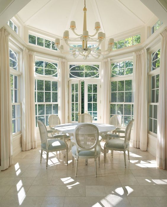 a rounded nook with lots of French windows, refined neutral and pastel furniture, a chic chandelier and lots of light coming in here