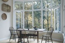 a rustic dining space with an oversized bow window with a gorgeous view, a simple wooden dining set and decorative baskets