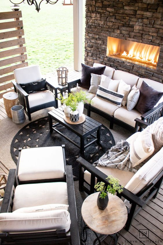 a rustic outdoor space wiht a stone clad fireplace, black furniture with white upholstery, a black table and a black jute rug, a chandelier is cool