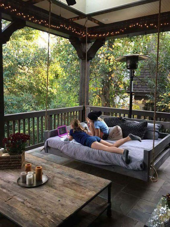 a rustic porch with a large hanging daybed, a reclaimed wood coffee table, some string lights, candles and blooms around