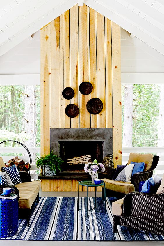 a rustic porch with a stone fireplace and a wood cover, simple dark wicker furniture, decorative plates and printed and neutral textiles