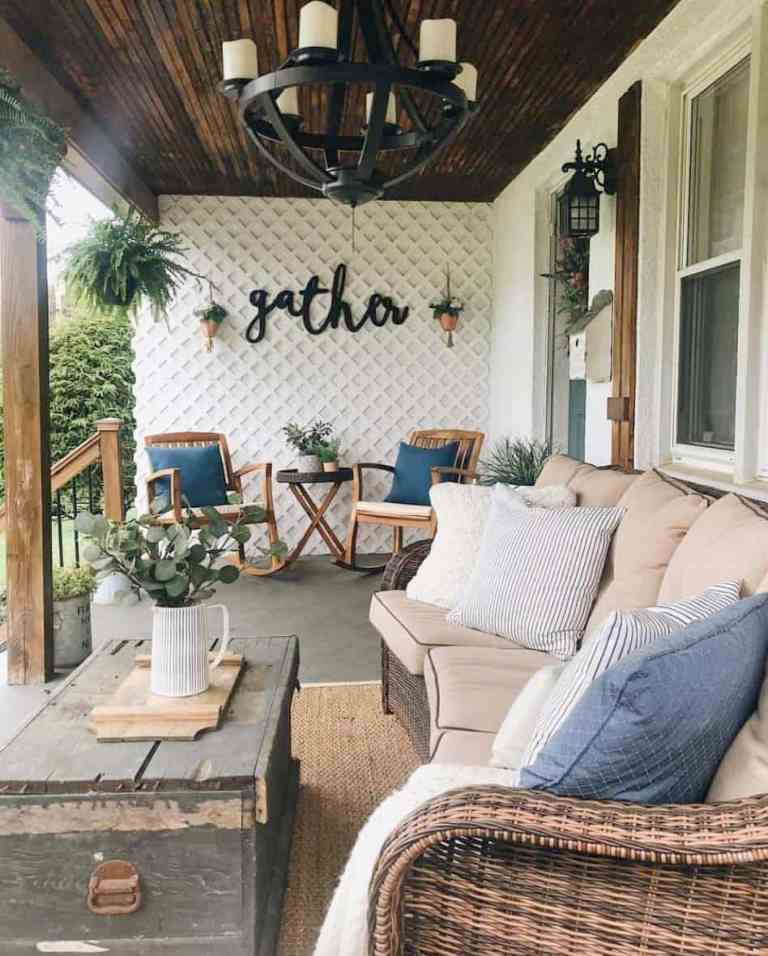 a rustic porch with wooden rockers, a coffee table, potted greenery, a wicker sofa with printed pillows and a chest coffee table
