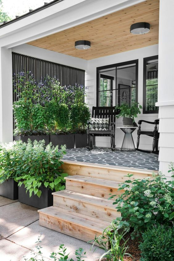 a rustic summer porch with black rockers and a table, lots of greenery and blooms and a printed rug is a bold and contrasting space