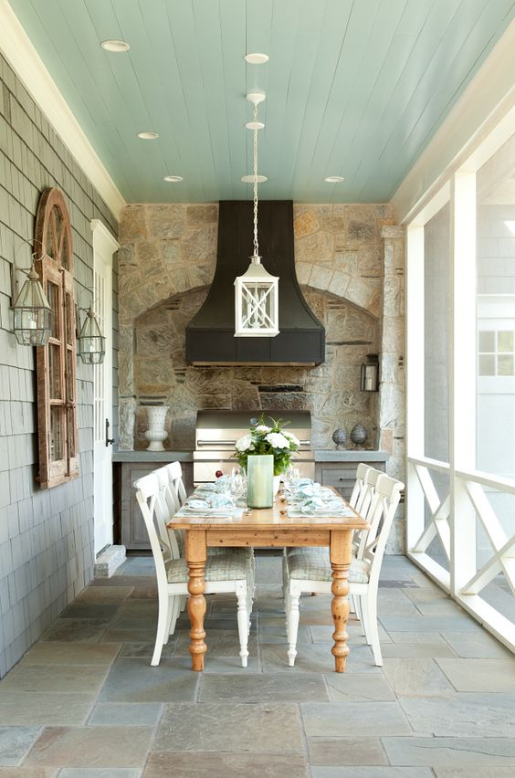 a screened porch with a kitchen and dining furniture, with built-in lights and pendant lamps is a lovely space