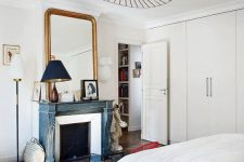 a serene Parisian bedroom with built-in wardrobes, a fireplace with a blue mantel, a large mirror in a gilded frame and a bed with neutral bedding
