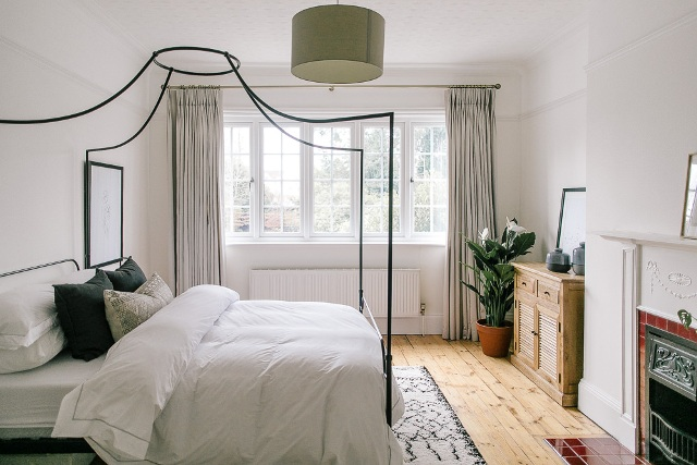 a serene bedroom with a meta fireplace, a canopy bed with neutral bedding, a stained dresser, neutral textiles and potted plants