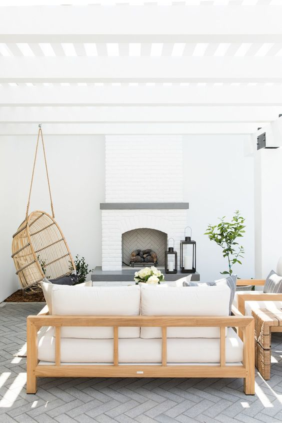 a serene outdoor space with a brick fireplace, light stained furniture, printed pillows, a hanging rattan chair and some greenery