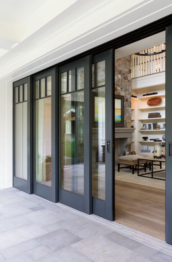 a series of black sliding doors leading to the garden allow to open the living room to outdoors completely and easily